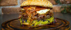 Dry Aged Beef Burger mit Fried-Pickled-Onions und Erbsenpüree