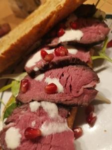 Filetsteak auf Zwiebelbaguette mit Caesar Salad und Granatapfelkernen